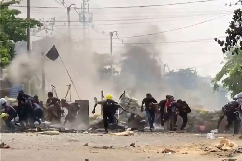 緬甸仰光反政變示威者29日在臨時路障爆炸後倉皇逃離。(法新社)