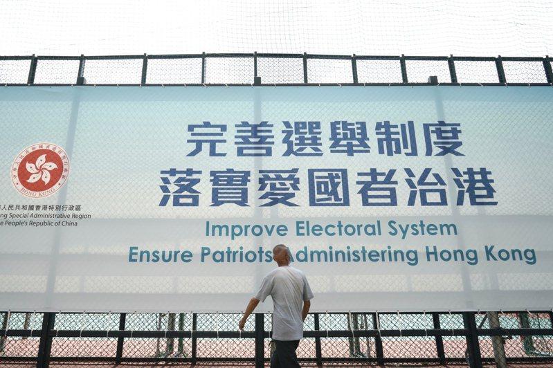 大陸全國人大常委會昨通過香港基本法附件一和二的修訂案,北京加強對香港的全面管治權。圖為港府在香港街頭設置的修改選制宣傳看板。(美聯社)