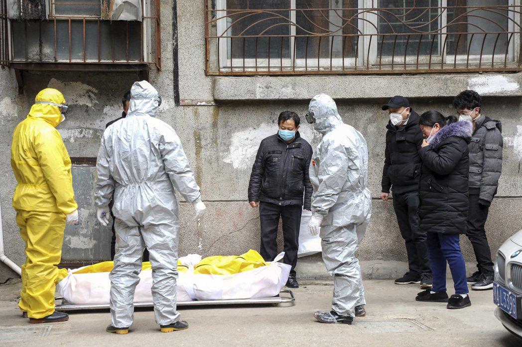 圖為2020年2月,殯儀館人員從武漢一棟大樓裡移走一名疑似死於病毒的當地居民。 ...