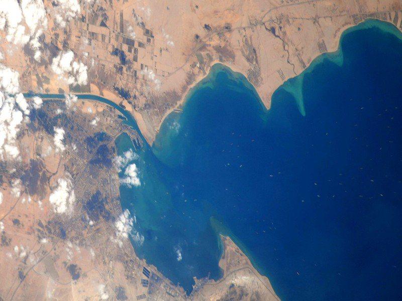 日籍太空人野口聰一在推特上分享一張蘇伊士運河大排長龍的空拍照,可以看到海面上有許多白點的船舶長龍。 圖/野口聰一推特