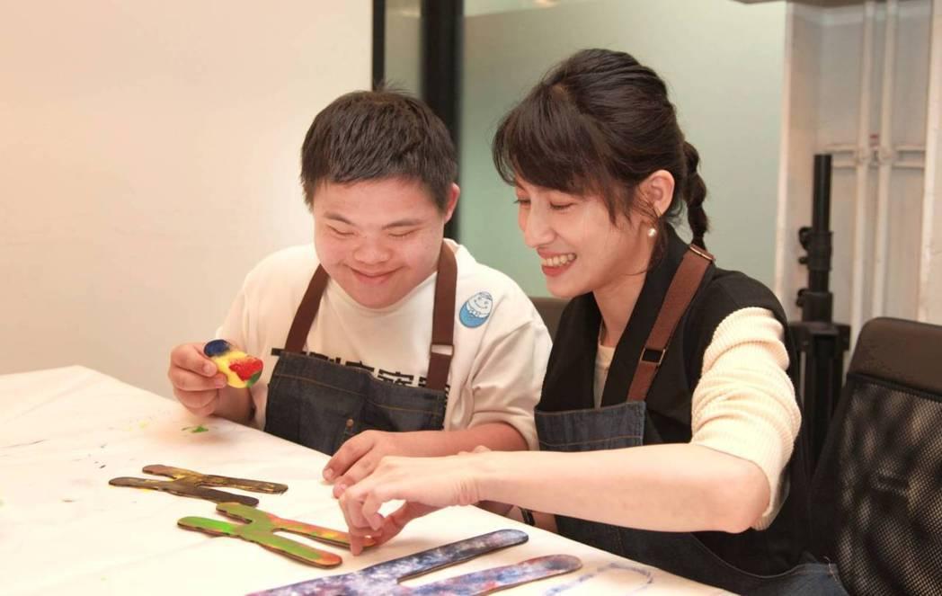 連俞涵(右)與唐寶寶共同創作代表唐寶寶的染色體。圖/唐氏症基金會提供