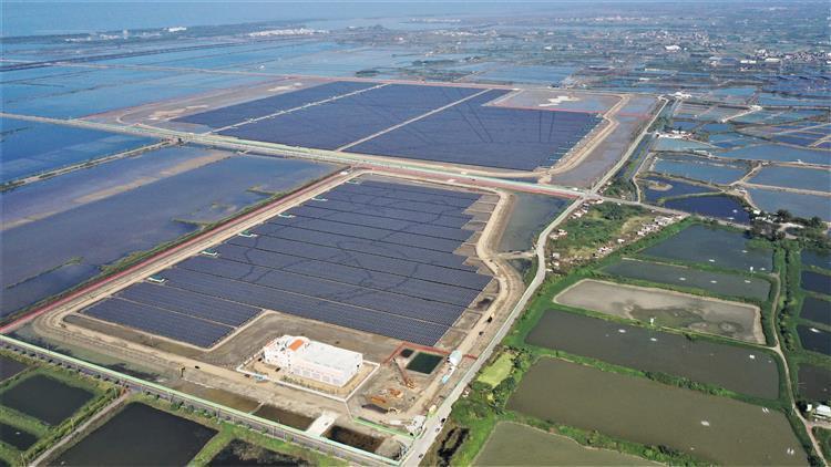 台電繼2019年在彰濱工業區完成當時全國最大的100MW太陽光電場,進一步利用台南將軍、七股區214公頃、等同300座足球場大的廢棄鹽灘地,用48萬片光電板再度打造全台地面最大、裝置容量達150MW(15萬瓩)的台南鹽田太陽光電場。圖/台電提供