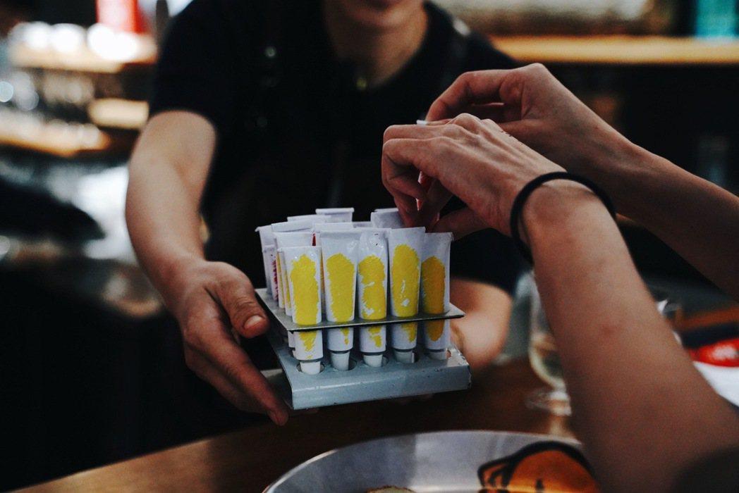 第二套餐點可以拿起裝入經典調酒「柯夢波丹」與「蜂之膝」風味果膠的紅、黃油畫管於盤...