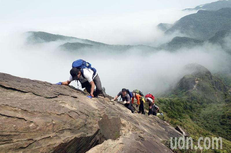06黃金稜線「劍龍稜-鋸齒稜」,攀爬在岩壁腳底雲霧繚繞。記者曾吉松/攝影