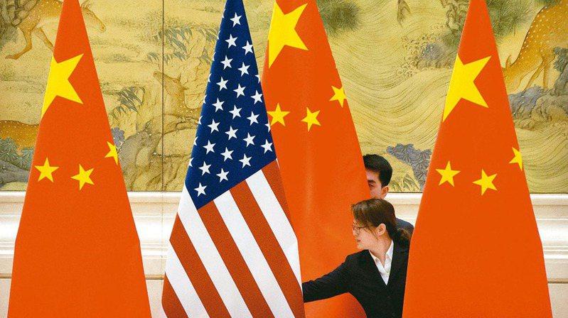 美國貿易代表署報告指出,中國大陸的產業政策是造成多個產業產能過剩的「世界禍首」。圖為2019年2月美中舉行貿易協商前,一名中國大陸員工調整美中國旗的資料照片。(美聯社)