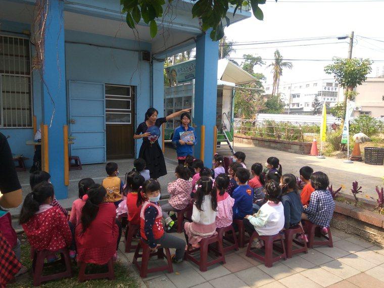 高雄市南安國小教務主任莊錦英在樹下與孩子說故事。圖/教育部提供