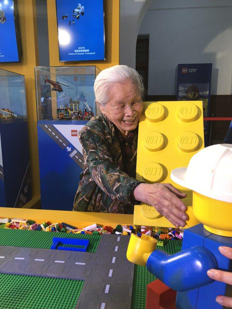 高齡92歲的老婦李何素鸞是樂高迷,最近還拼出兒時回憶的三合院,昨天也來朝聖新竹樂高積木展,開心玩起樂高。圖/新竹市政府提供