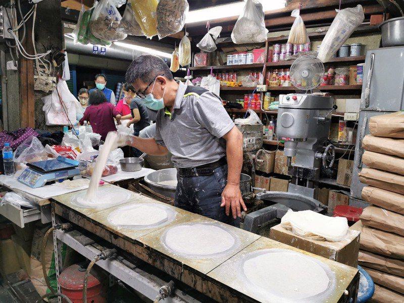 蔡政勳手一甩、2秒在烤爐擦1張皮,隨即換爐再甩,後面的人則跟著不斷收皮,包裝秤重販售。記者卜敏正/攝影