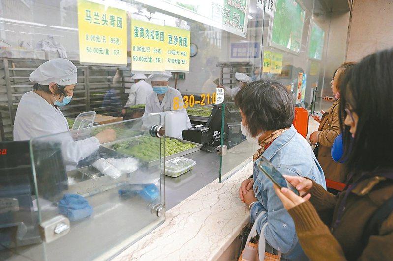 清明時節,上海一家老字號青團銷售火爆。圖為民眾在店內購買青團。(中新社)