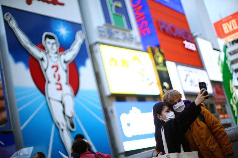 日本大阪府今天通報新增新冠肺炎確診719例,創新高紀錄。圖/路透社