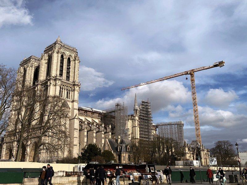 巴黎聖母院右側遠景,吊臂隨伺在旁,外牆安裝上新的鷹架。(中央社曾婷瑄)