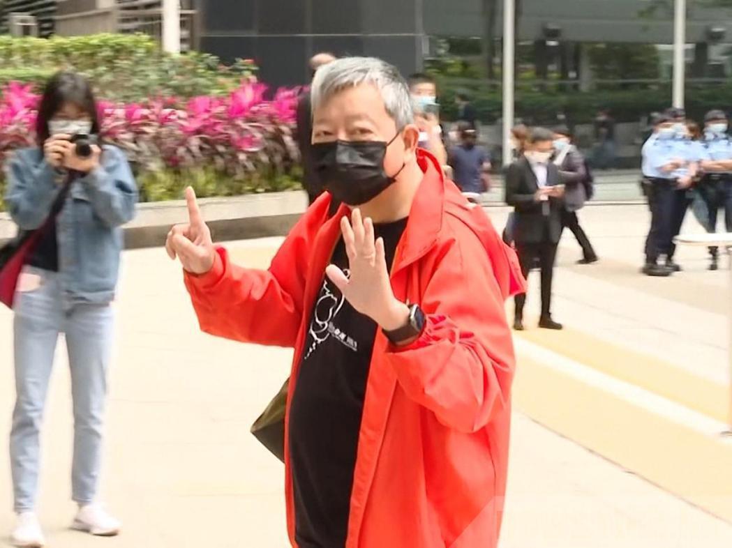 李卓人進入法庭前展示手勢,他表示,「我認罪但我沒做錯,歷史將判我們無罪」。(香港...
