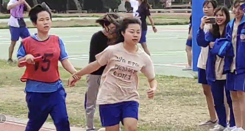 二林高中全盲女學生小蓁(左一)今天由同學拉著手,一起跑大隊接力,前面同學全力衝刺拉開距離,讓小蓁可以安心的跑,這一幕感動許多人。圖/校方提供
