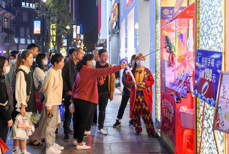 武漢「解封」一年了,夜幕下的武漢,民眾逛街吃飯休閒,感受城市夜生活的魅力。圖為市民在武漢市江漢路步行街活動。(新華社)