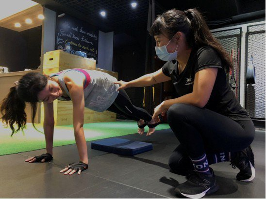 Beyond Fitness教練仔細地調整學員姿勢,防止在運動的過程受傷,讓健身...