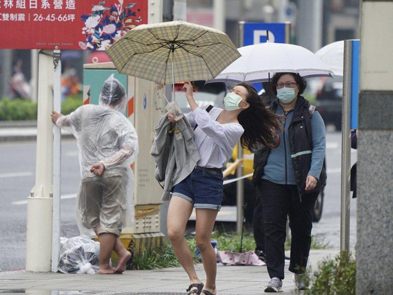圖為午後民眾街頭撐傘避雨,突然一陣強風,差點把雨傘吹掉。中央社