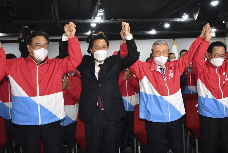 南韓國民力量黨候選人吳世勳(中)七日在首爾市長補選中大勝,在首爾黨部振臂慶功。(美聯社)