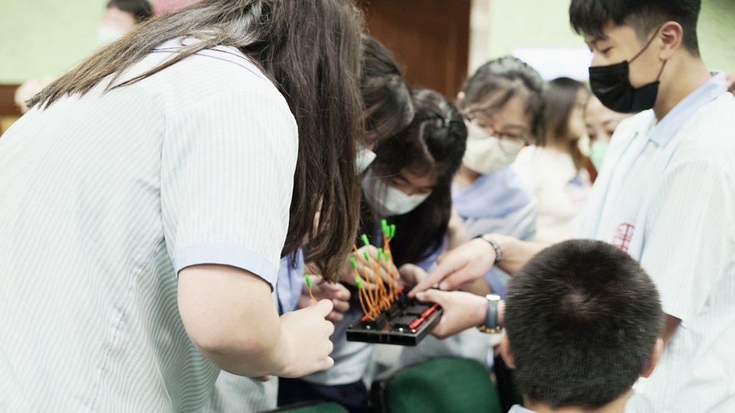 學生專注地嘗試接上電子火頭,體驗製作煙火的其中一步驟。鴻海/提供