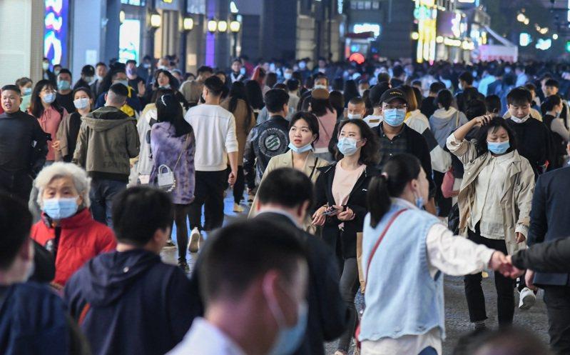 武漢解封滿周年,夜幕下的武漢街頭人潮眾多。(新華社)