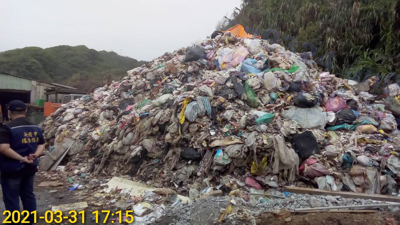 新北石門區有清潔公司在保護區堆放大量垃圾成山,新北環保局要求4月21日前將廠區內廢棄物清除改善完成。圖/新北環保局提供
