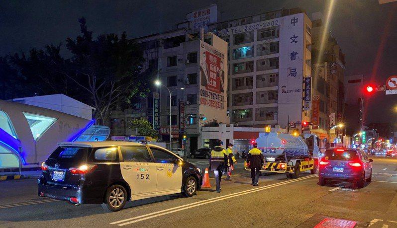 台中市一輛自來水公司的水車在9日深夜卡在中區台灣大道、興中街,警方到場交通指揮,避免追撞。記者陳宏睿/翻攝