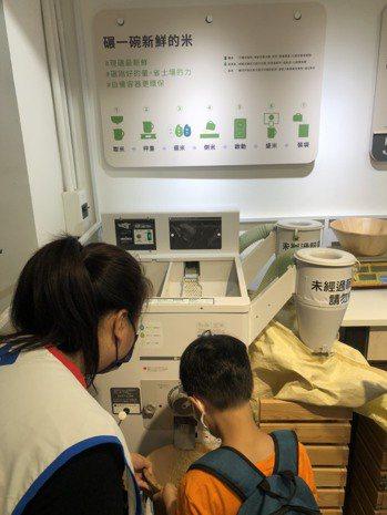 親子第一次體驗碾米,並以自備容器盛裝剛碾好、溫熱的米。記者胡經周/攝影