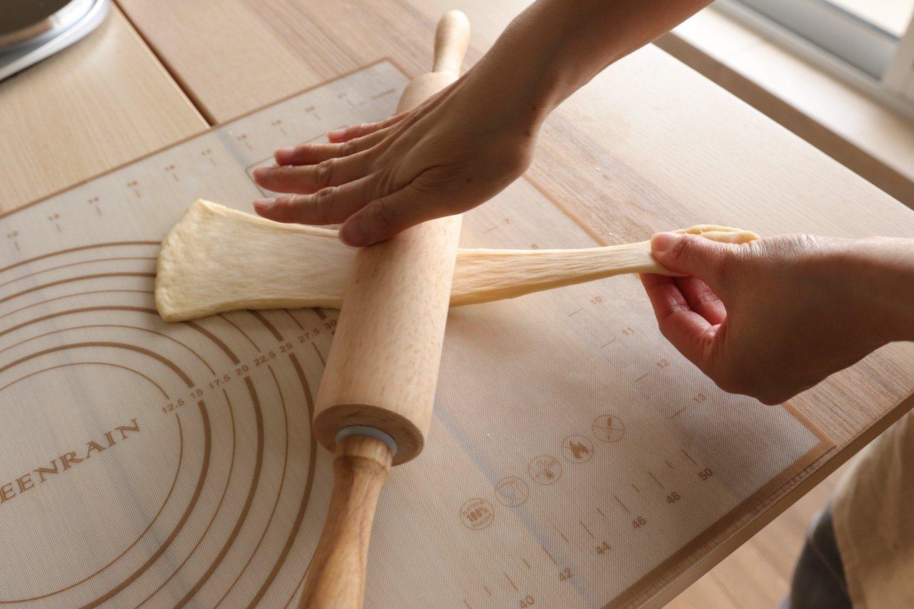 擀平麵糰,並輕拉長尾端,細端處靠近自己。 圖/如何出版社提供