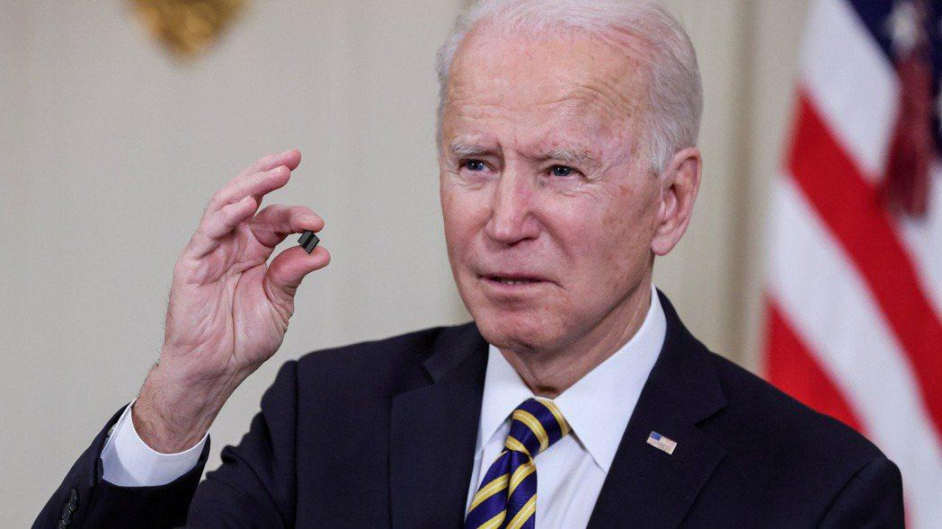 美國總統拜登2月24日手持晶片,表達對晶片短缺問題的關切。   路透