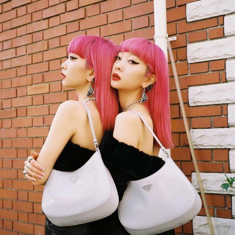 日本鈴木雙胞胎姊妹花Aya及Ami配戴PRADA垂墜式三角Logo耳環。圖/摘自...