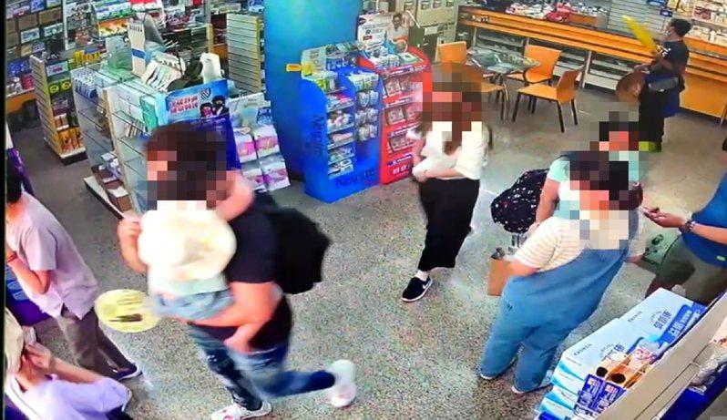 黑衣男子抱著女童走進藥局,尋求協助。記者莊祖銘/翻攝