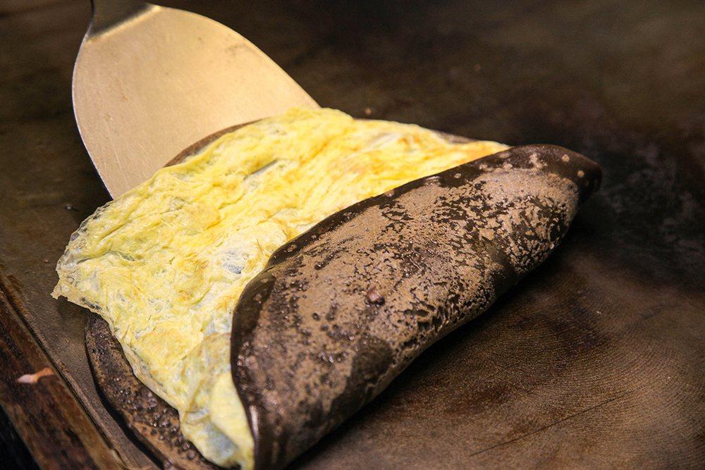 粉漿蛋餅做法是將麵糊在鐵板上煎得表皮焦香,再包入內餡捲起。  圖/李瑰嫻 攝影