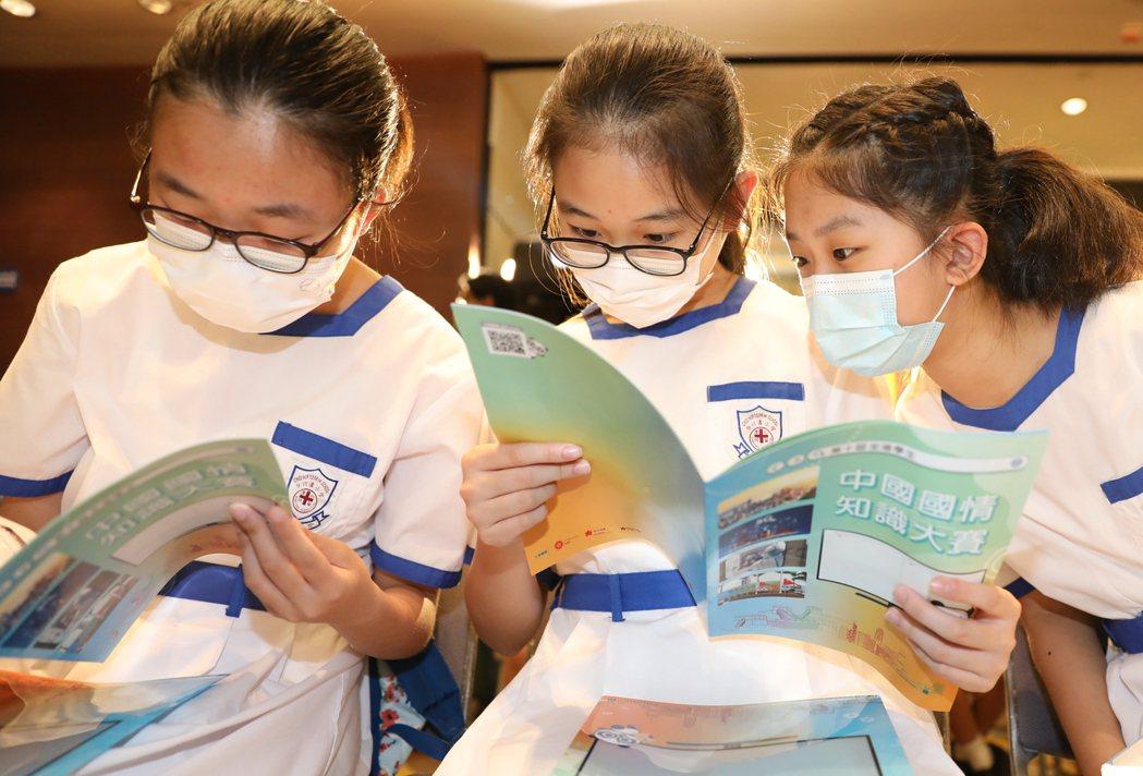 圖為香港學生中國國情知識大賽頒獎,獲獎學生閱讀大賽資料。(新華社)