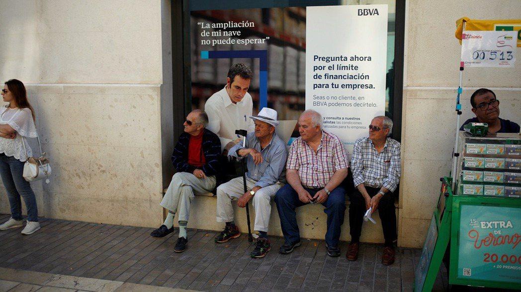 西班牙一群退休人士坐在馬拉加市中心一處西班牙外換銀行(BBVA)分行窗外,攝於2...