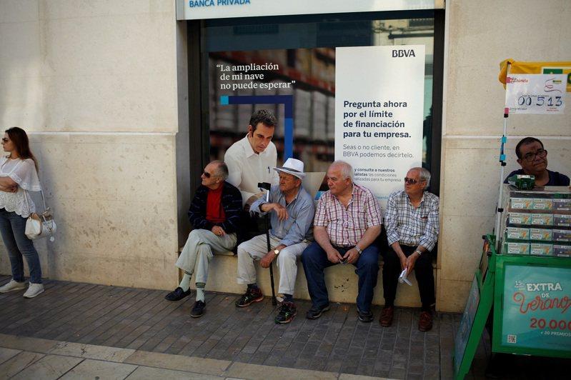 西班牙一群退休人士坐在馬拉加市中心一處西班牙外換銀行(BBVA)分行窗外,攝於2018年。西班牙社會安全部長埃斯克里瓦12日宣布,正在研究吸引勞工延後退休的激勵措施。 路透