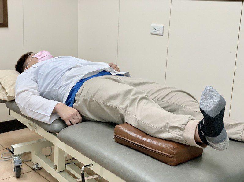 第一招「腳踝幫浦」運動,在患肢小腿墊上毛巾(或較硬質枕頭),腳踝往上勾、之後往下壓,每回30-40下,可降低術後水腫。記者王昭月/攝影