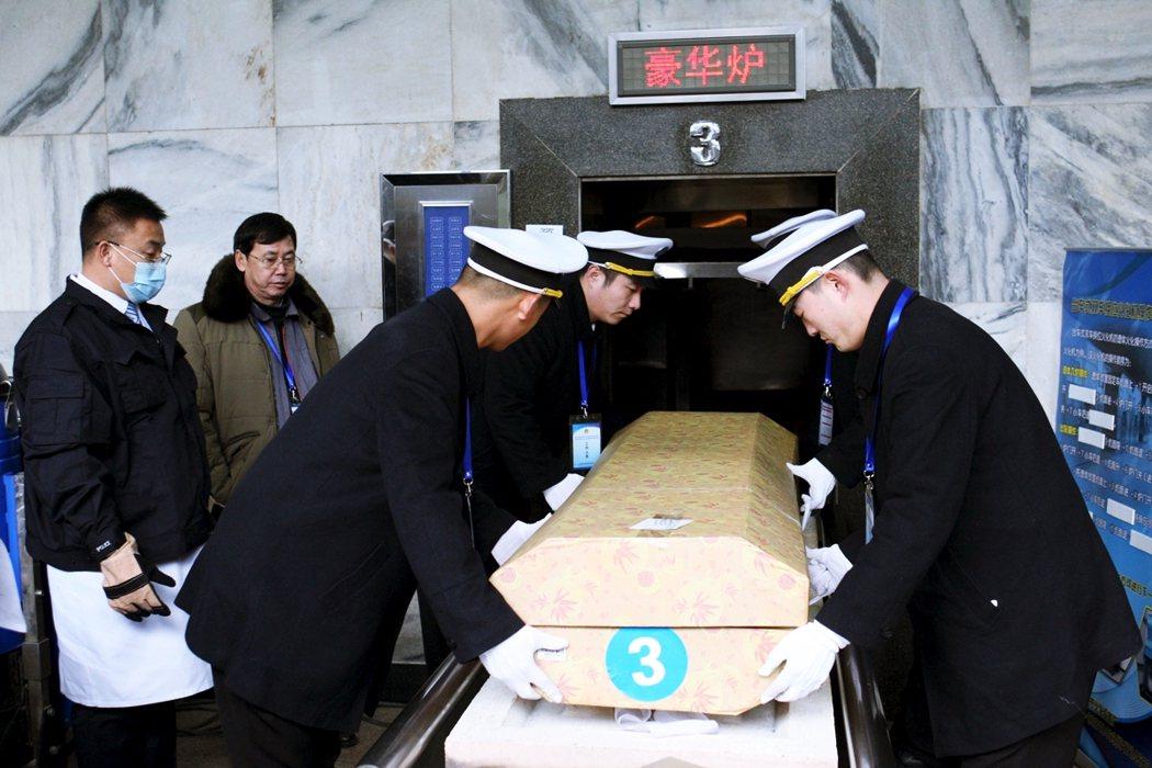 示意圖,圖為2015年中國火葬技術人員參加北京舉辦的火葬技術競賽時,將棺材放入火...