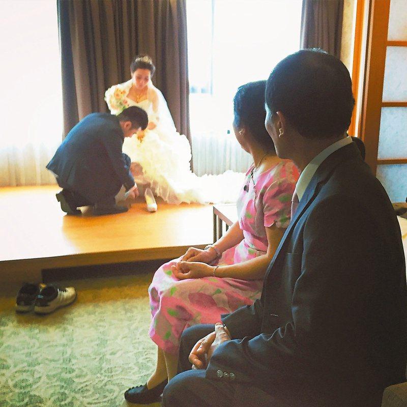 新郎幫新娘穿鞋,習俗一種。(圖/孫梓評提供)