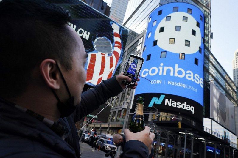加密貨幣交易所龍頭Coinbase於14日掛牌上市,一名員工手拿一瓶香檳,在那斯達克外拍照留念。美聯社