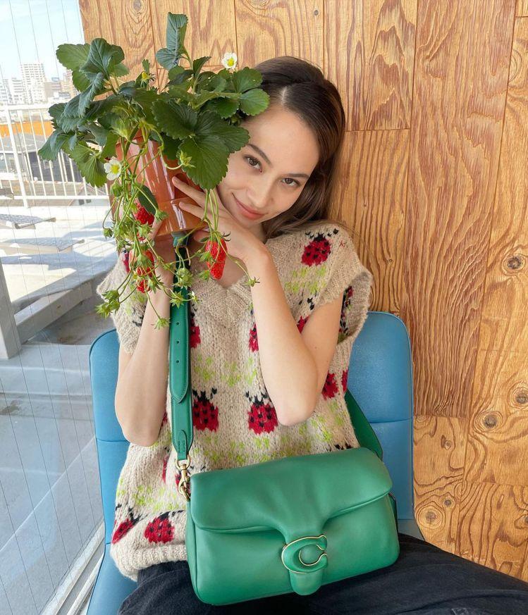 水原希子身穿COACH瓢蟲主題毛衣20,800元、搭配綠色Pillow Tabb...