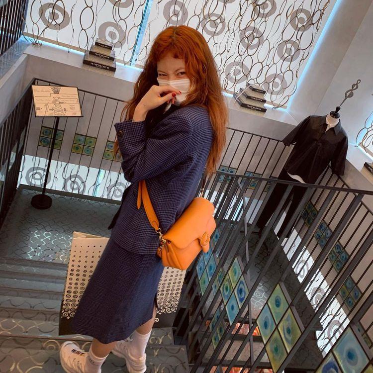俏皮可愛的泫雅以蜜餞橙COACH Pillow Tabby作為逛街手袋。圖/取自...