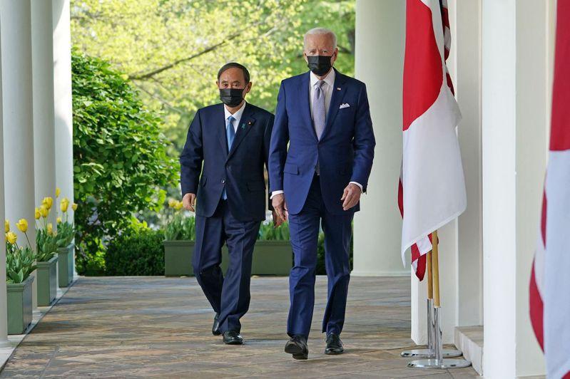 美國總統拜登(右)與日本首相菅義偉(左)十六日前往白宮玫瑰花園參加聯合記者會。(法新社)