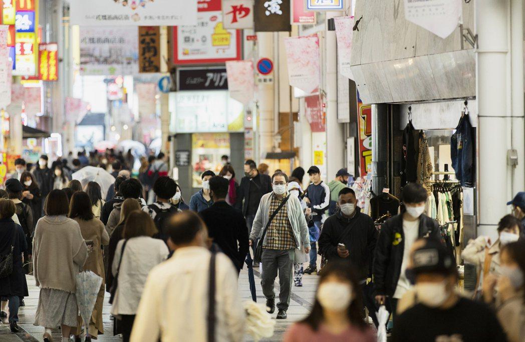 日本大阪民眾十七日帶著口罩經過熱鬧的難波區一條購物街。(美聯社)