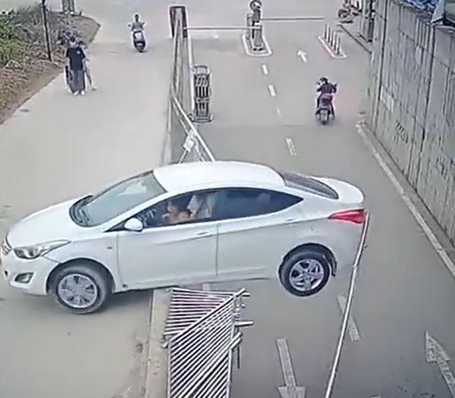 一名女子準備倒車離開,不料車子突然加速轉彎往後衝,並且撞破護欄,因為後方馬路低了好幾公尺, 車子一半就這樣懸在空中,驚嚇度破表。圖/翻攝YouTube「NO HERO」上傳影片