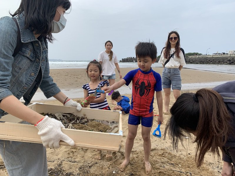 靈鷲山佛教教團今天號召志工在福隆東興宮挖子海灘淨灘,並用篩網濾出沙中的小垃圾。圖/靈鷲山佛教教團提供