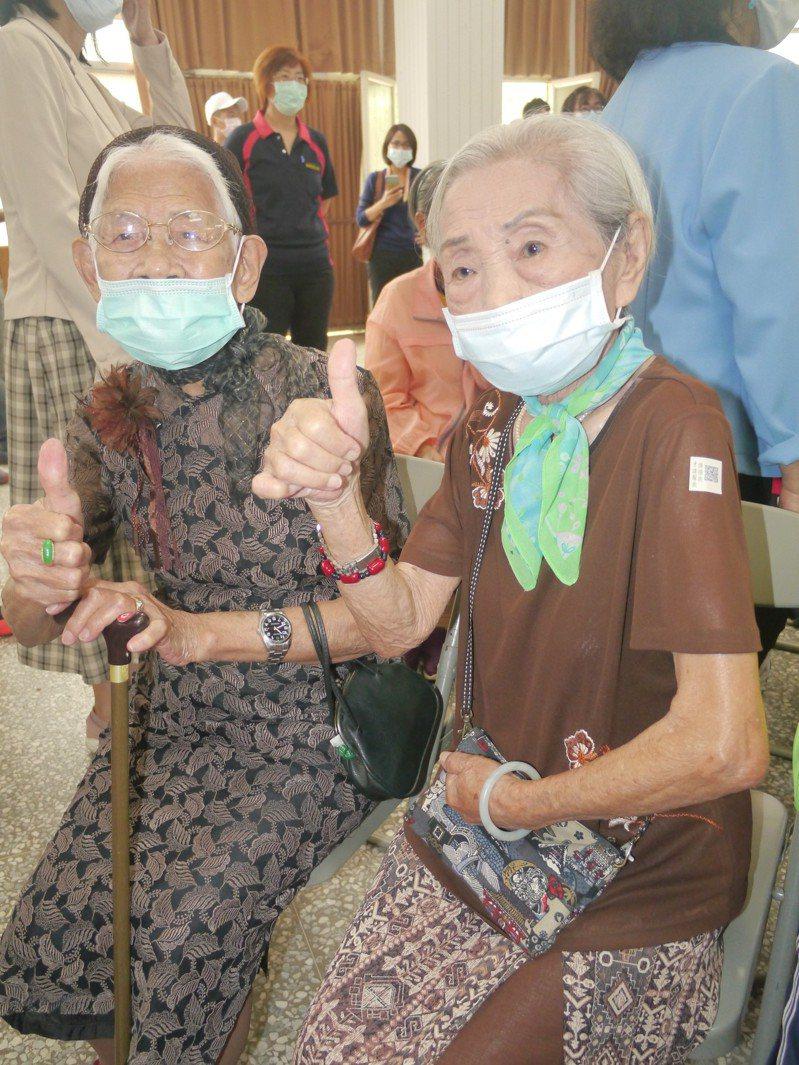 兩味老奶奶盛裝出席捐贈活動,97歲楊奶奶(右)將守護貼黏在手臂上。記者徐白櫻/攝影