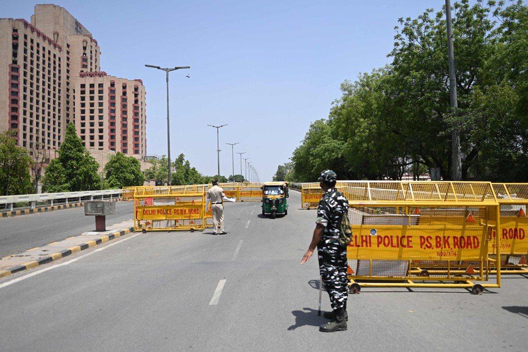 新德里在周末期間已實施封鎖來應對疫情,圖為18日警方在市區道路上設置的攔檢點。法...