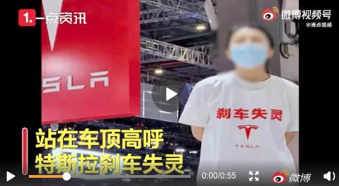 19日,在2021上海車展上,一名女士身穿「剎車失靈」字樣的T恤,站到一輛特斯拉...