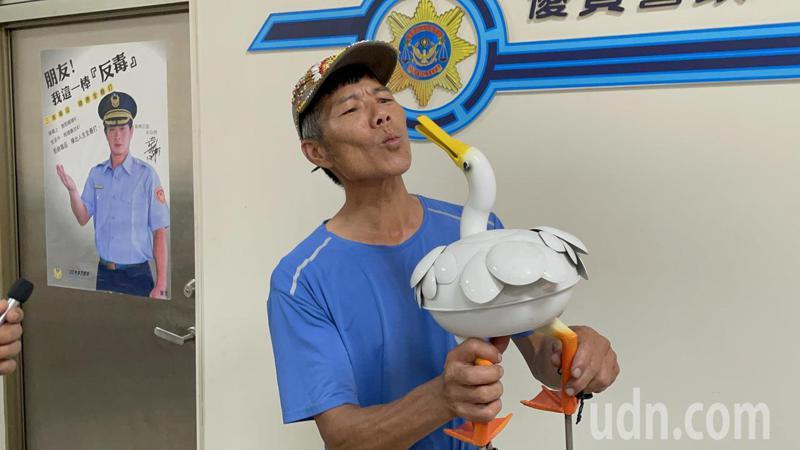 藝術家賴銘傳日前在嘉市北香湖公園展出的鴨子不見,他今天到嘉市第1警分局領回,作勢親吻。記者林伯驊/攝影