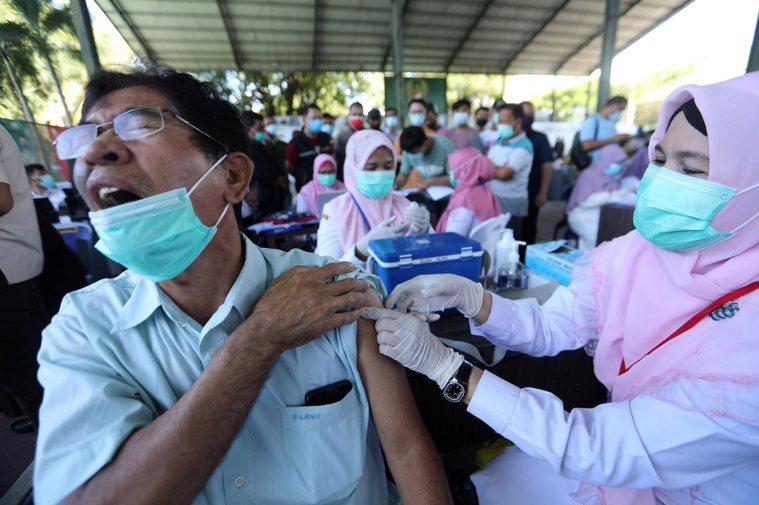 醫護人員廿日在印尼班達亞齊為民眾注射新冠疫苗。雖然各國加快施打疫苗,但疫情未見緩...