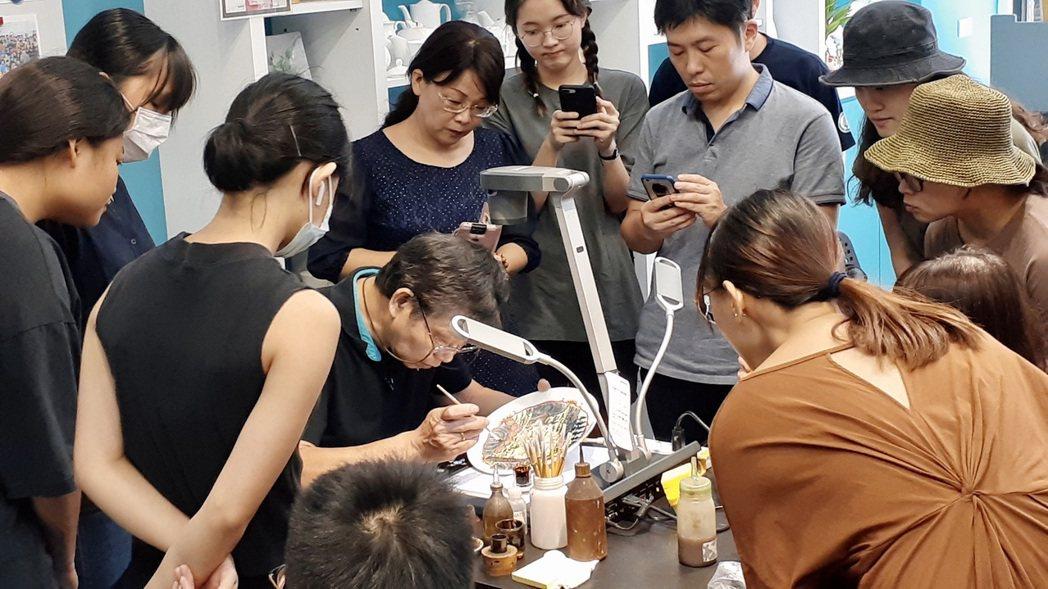 林發權老師(中)與北科大文發系學生分享釉上彩繪工藝技法。 北科大/提供